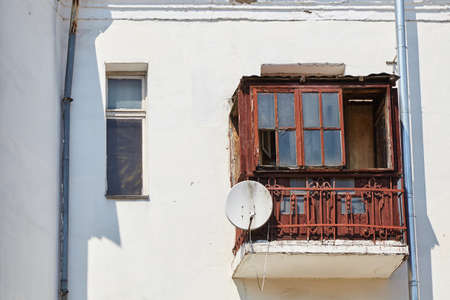 Old wooden balcony in dilapidated condition with a satellite dish