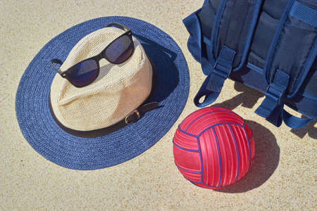 Straw hat, sun goggles, blue backpack and red water polo ball
