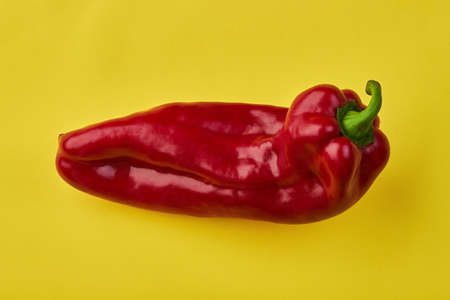 Red pepper of an unusual shape on a yellow background