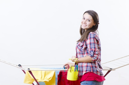 A smiling woman putting clothes to dry photo