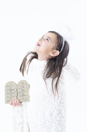 bible ten commandments: A little girl dressed as angel holding ten commandments