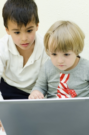 man using computer: Two children staring at laptop