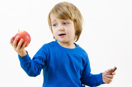 perplexed: A perplexed blond boy fighting with food temptation Stock Photo