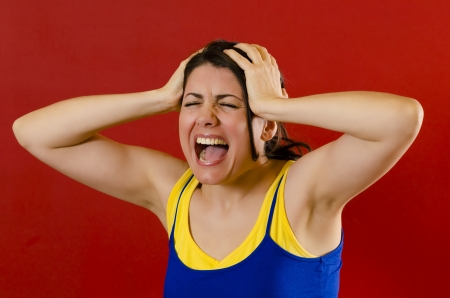 Angry woman screaming loud , isolated on red