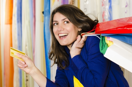 Shopaholic: A shopaholic girl holding a credit card coming from shopping