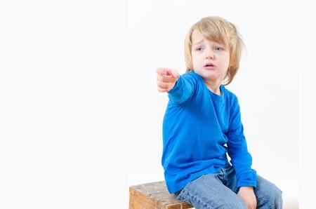 sad boy: A cute sad boy pointing his finger to something imaginary