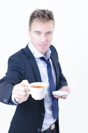 A hospitable man holding a cup of beverage photo
