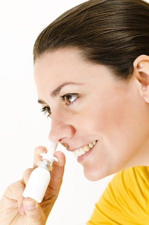 A happy woman using nasal spray