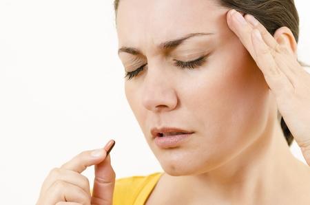 Young woman having a headache holding a pill