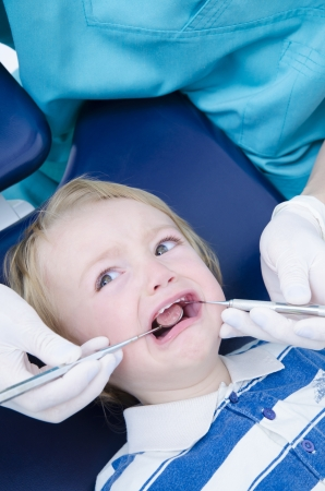 A dentist examining a kid with specialized instruments