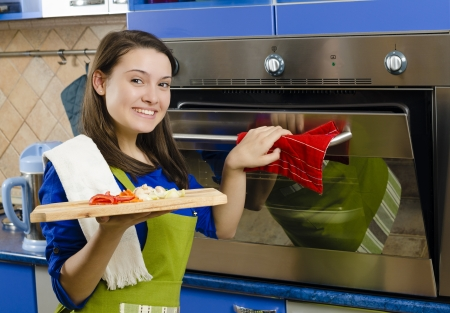 Beautiful smiling woman makes baked food photo