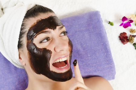 Attractive young woman getting a chocolate facial mask in the beauty spa photo