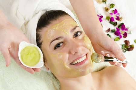 Attractive young woman getting a facial mask in the beauty spa photo