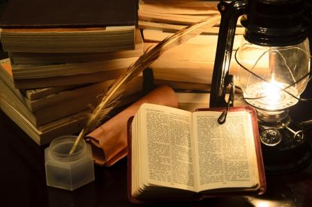 ランプの光の中で聖書 surrunded 本します。