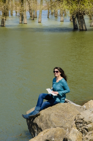 Woman Relaxing in a landscape with forest, river and stones photo