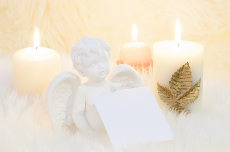 an angel surrounded by candles holding a empty sheet for wish list