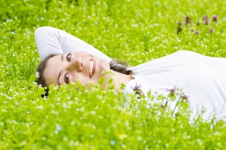 Beautiful young woman relaxing in grass photo