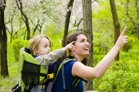 mochila viaje: Una joven mujer de trekking con su beb� que se�ala en alguna Foto de archivo
