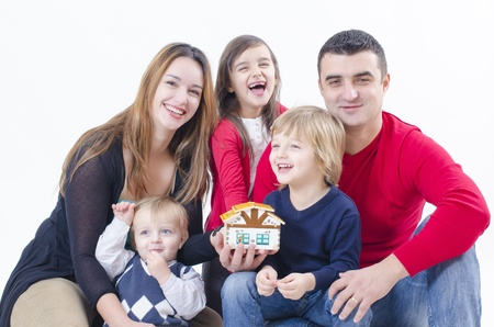 A family with three children holding a little house