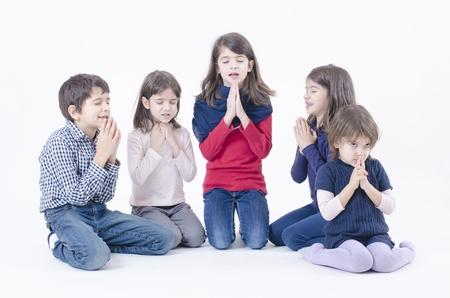 familia orando: Cinco niños rezando aislado en blanco