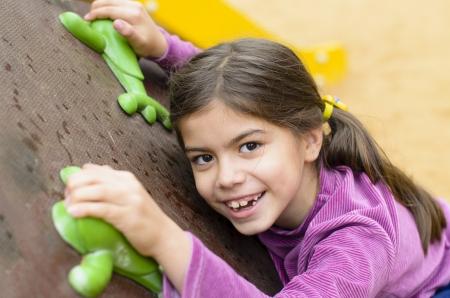 Kleines Mädchen auf einer Kletterwand in einem Park