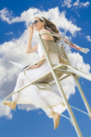 A young woman enjoying the life with an laptop on lifeguard chair