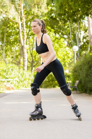 roller blade: Sporty Woman with skates in a park Stock Photo