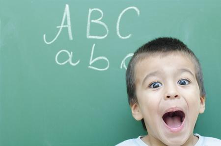 Little Boy Screaming Very Happy at Blackboard photo