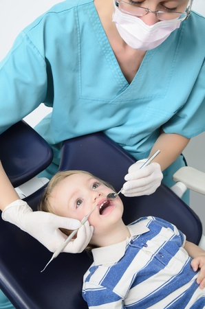mouth cavity: a dentist examining a kid with specialized instruments Stock Photo