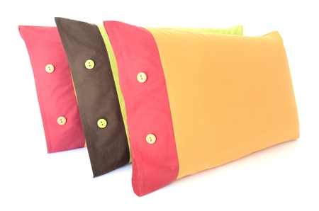 overlapped: three colored pillows with buttons isolated on white
