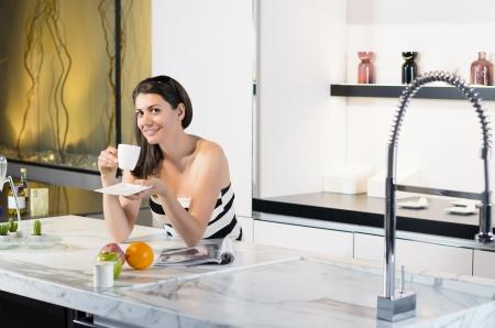 Beautiful woman enjoying new kitchen photo