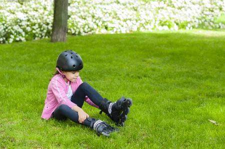 niño en patines: Muchacha deportiva con los patines en un parque Foto de archivo