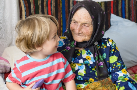 Great grandmother and her great grandson in a rustic home Standard-Bild