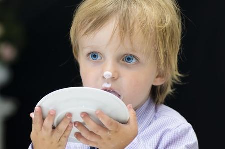 plato del buen comer: Little Boy que lame el plato sobre fondo negro Foto de archivo