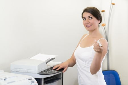 office printer: Young business woman making copies at the office Stock Photo