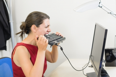 Angry businesswoman biting the keyboard