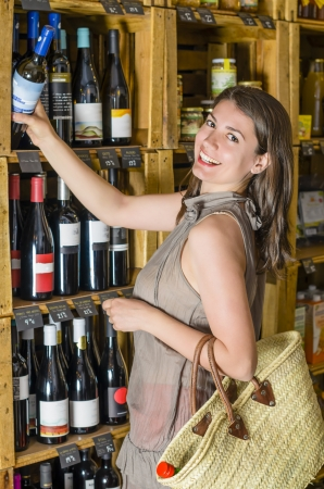 choose person: Young woman is choosing wine in the supermarket