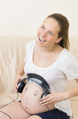 Pregnant woman relaxing with smiley face and headphones photo