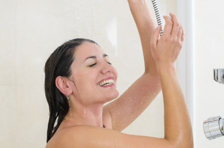 mujer bañandose: Mujer que toma una ducha disfrutando de las salpicaduras de agua en su
