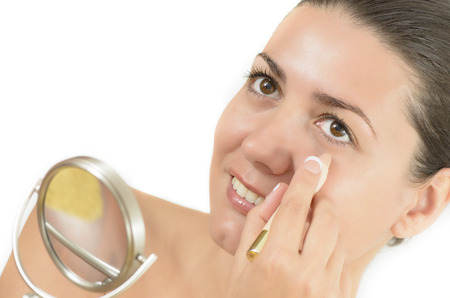 correcting: Young woman using concealer looking in the mirror