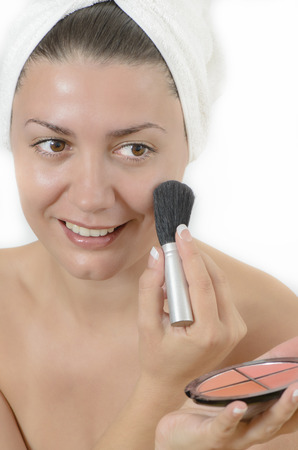 Young woman applying make up with a brush photo