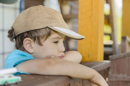 wistful: A wistful child on his porch Stock Photo