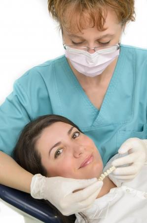 A dentist showing porcelain teeth to patient Standard-Bild