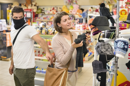 Dief steelt van handtas van een vrouw in een winkel Stockfoto
