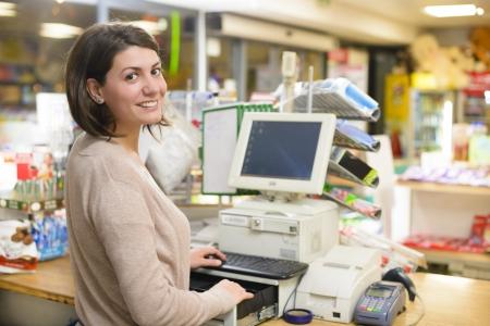 abarrotes: Mujer joven en la caja registradora en una tienda Foto de archivo