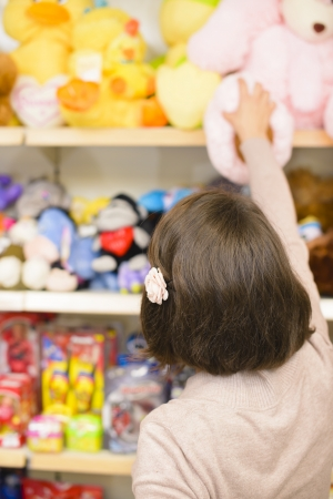 toy shop: Young woman picking toys in a store