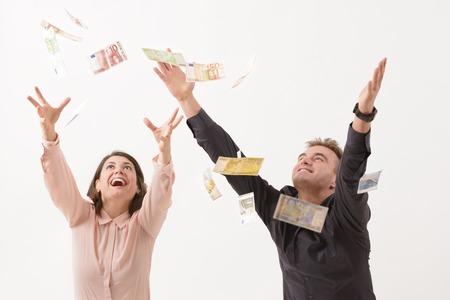winning business woman: Young couple catching falling money