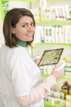 vendedor: Farmacéutico de sexo femenino joven en una farmacia que trabaja en un Tablet PC