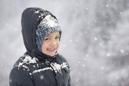 Happy Child in Wintertime snowflakes around photo