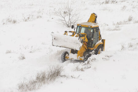 A snow tractor clearing the road from snow photo